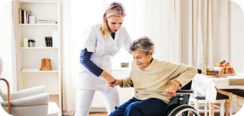 caregiver assisting senior woman in standing