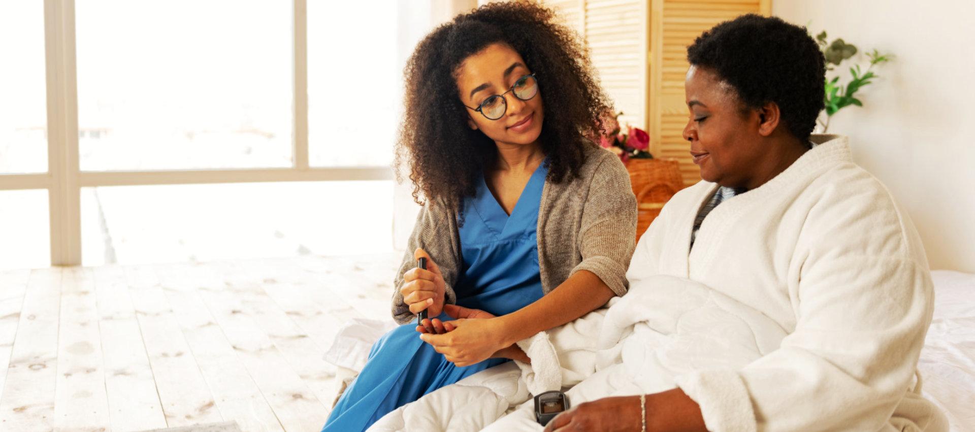 caregiver checking the sugar level of senior woman